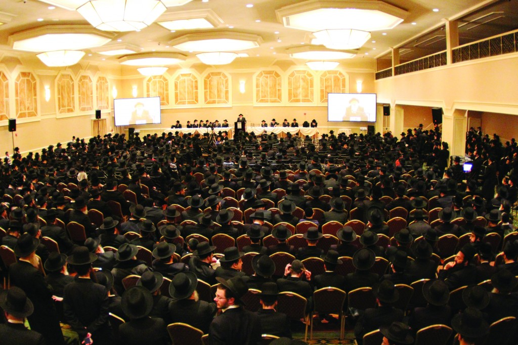 A crowd of close to 1,000 is addressed by the Novominsker Rebbe (at podium) at an asifah at The Palace in Boro Park, decrying the Israeli government's stated goal of drafting yeshivah bachurim for the army. (Hillel Engel)