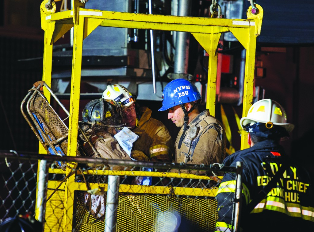 A worker, with black fire helmet at left inside a construction transport bucket, is rescued from an MTA subway construction project. (AP Photo/Craig Ruttle)
