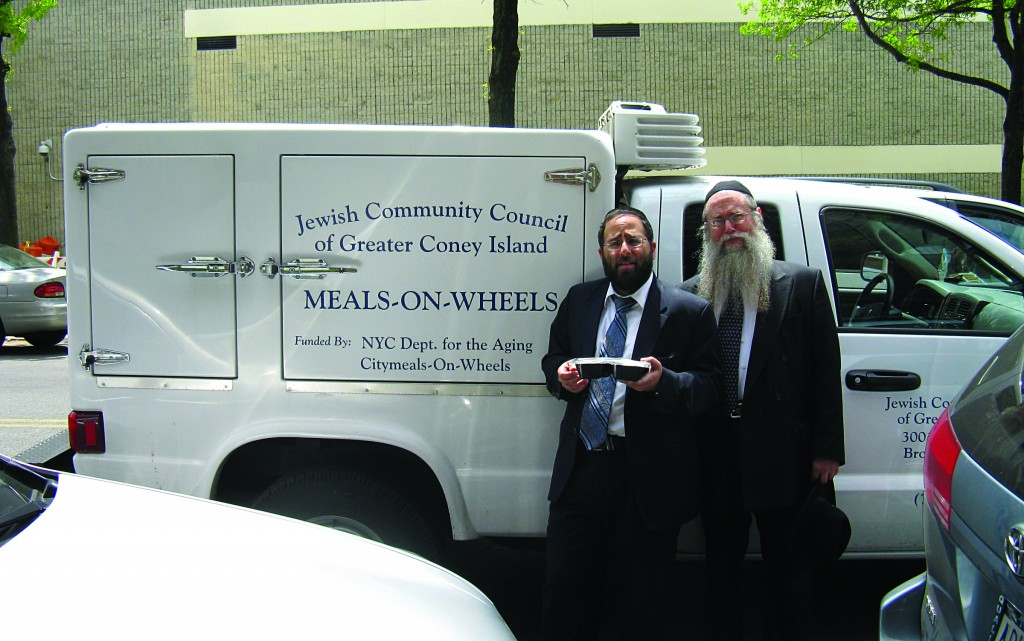 Rabbi Saul Maslaton (L), spiritual leader of Ahi Ezer Congregation, and Rabbi Moshe Wiener, executive director of the JCCCGI, alongside one of Ocean Parkway Senior Center's Meals-on-Wheels vehicles.