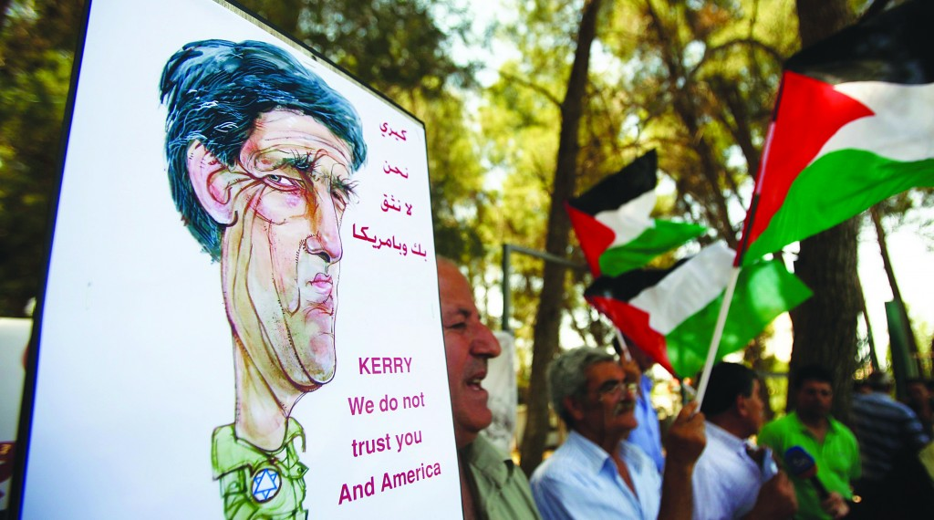 A Palestinian protester holds a poster with a caricature of Secretary of State John Kerry at a demonstration during Kerry's meeting with Palestinian Authority President Mahmoud Abbas in Ramallah on Thursday. REUTERS/Mohamad Torokman