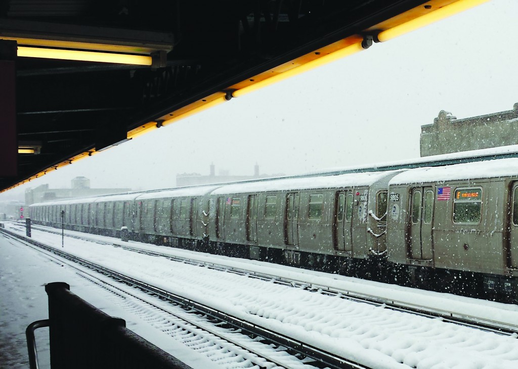 An F train leaves the 18th Avenue station in Boro Park Thursday morning covered in snow. (Shemayah Morgan)