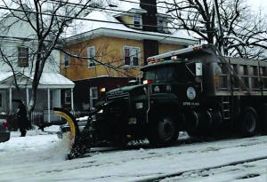 A snowplow roars down a road in Lakewood Thursday morning. (TheLakewoodScoop.com)