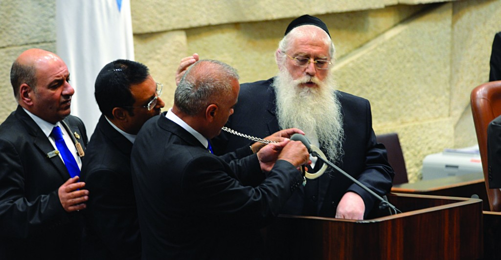 Knesset security attempting to remove the handcuffs from Rabbi Porush.