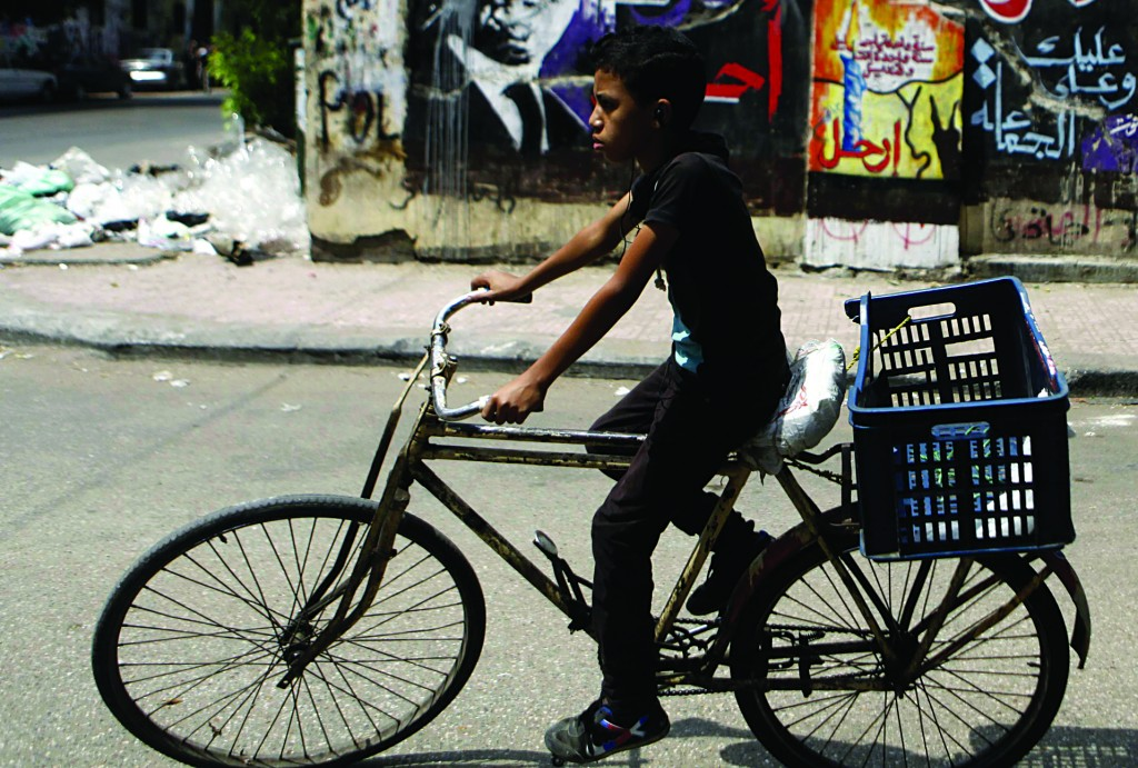 A boy cycles past graffiti depicting ousted Egyptian President Mohamed Morsi (L) and the Deputy Guide of the Muslim Brotherhood Khairat Al-Shater in downtown Cairo Monday. (REUTERS/Amr Abdallah Dalsh)