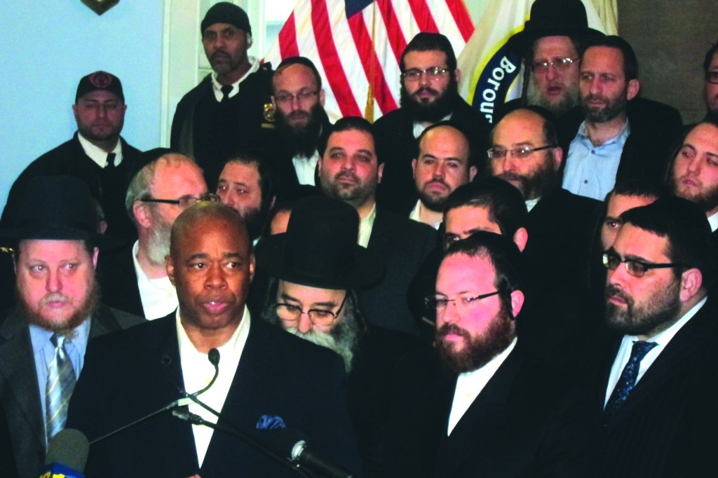 Brooklyn Borough President Eric Adams at the press conference Sunday in his borough hall, along with (L-R) Rabbi Chanina Sperlin, Yeruchum Silber, Aron Weider, Moshe Dovid Niederman, Shea Rubinstein, Isaac Lieder, Yanky Daskal, Meny Hoffman and Avraham Kahn. (Hamodia Photo)