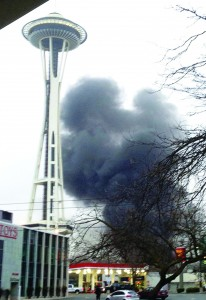 Smoke rises at the scene of a helicopter crash outside the KOMO studios near the space needle in Seattle on Tuesday. (AP Photo/KIRO-TV)