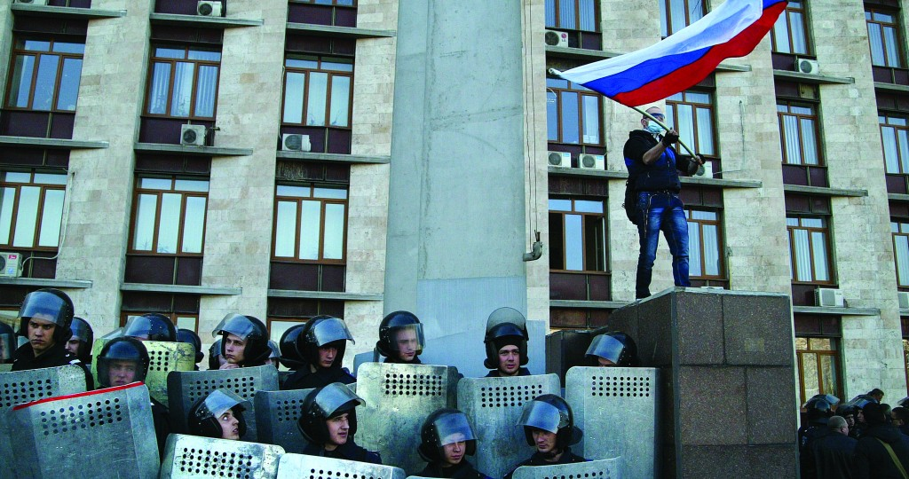 A pro-Russian masked activist waves a Russian national flag above Ukrainian police at the regional administration building in Donetsk, Ukraine, Sunday. (AP Photo/Alexander Ermochenko)