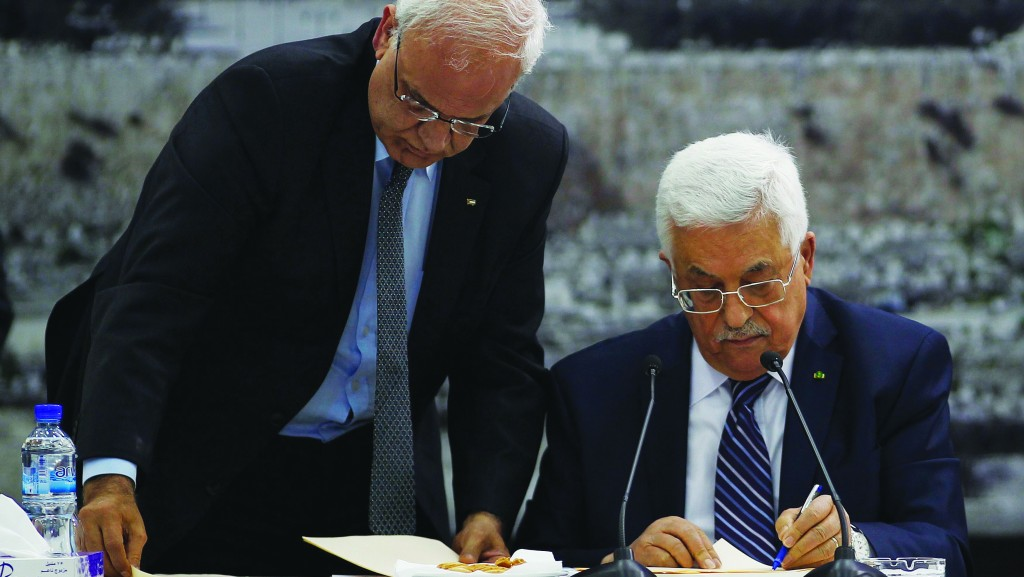 Palestinian chief negotiator Saeb Erekat (L) helps Palestinian Authority President Mahmoud Abbas as he signs international conventions in Ramallah. (REUTERS/Mohamad Torokman)