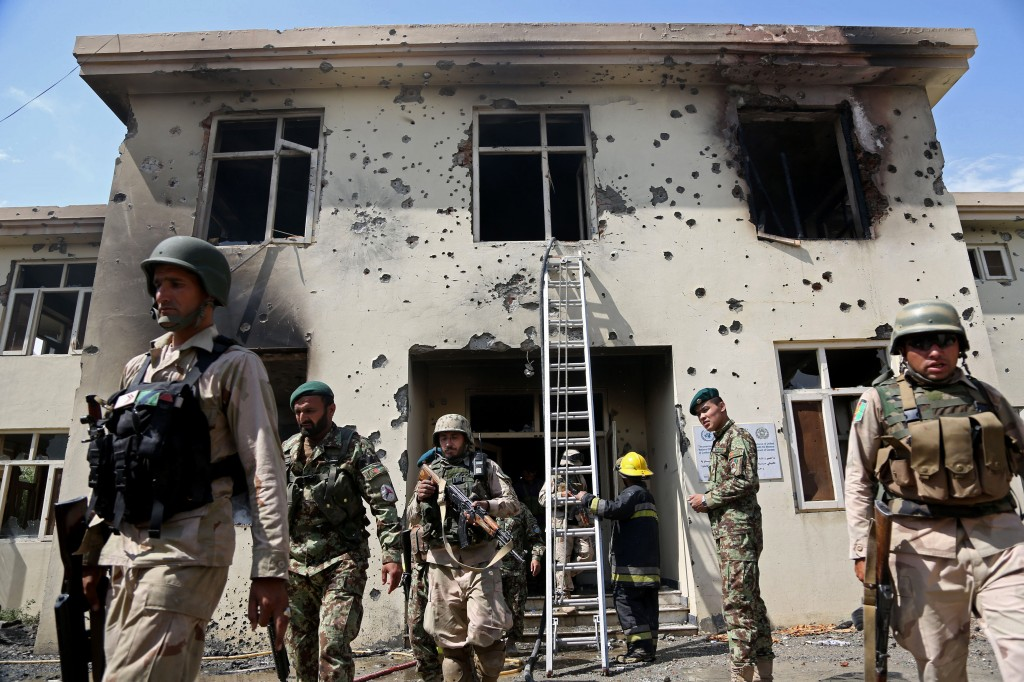 Afghan security personal surround the area after Taliban fighters stormed a government building in Jalalabad, east of Kabul, Afghanistan, Monday.  (AP Photo/Rahmat Gul)