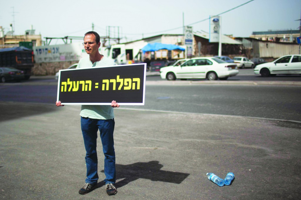 An Israeli protesting against adding fluoride to the water supply. The sign reads: Fluoridation = Poisoning. (Yonatan Sindel/Flash90)