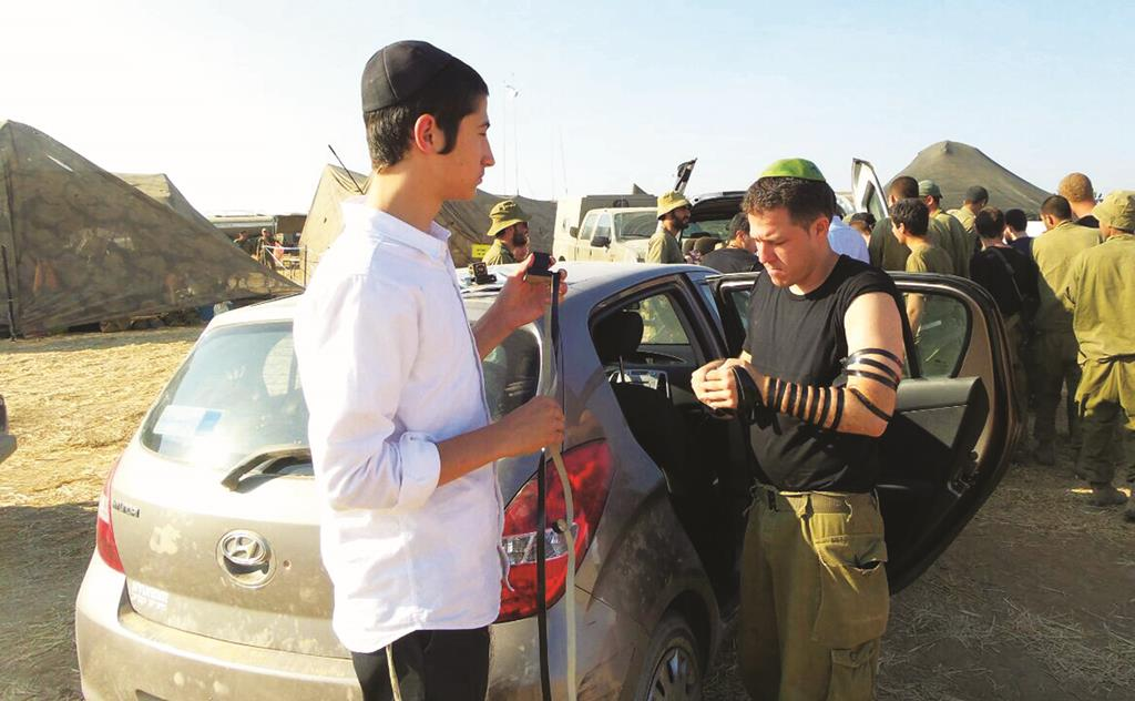 A Chabad shaliach, one of a group of Lubavitzcher Chassidim in New York who traveled to Eretz Yisrael to be mechazek Israeli soldiers, dons tefillin on a soldier near the border with Gaza.