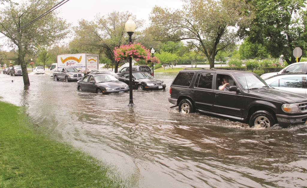 Firefighters on Wednesday cross a flooded Long Island intersection (L), while vehicles in Babylon maneuver down a flooded Montauk Highway. (AP Photo/Frank Eltman)