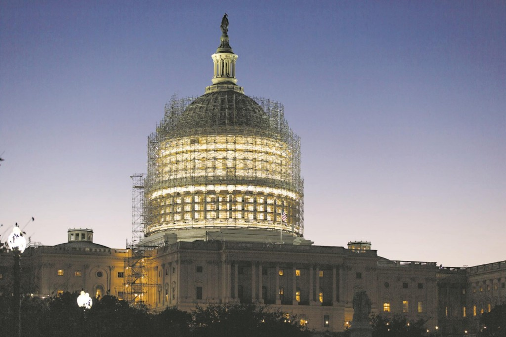 The dome of the Capitol building, nearly obscured by scaffolding at dawn in Washington, D.C.  The House and Senate are adjourned until after the midterm election.  (AP Photo/J. Scott Applewhite)