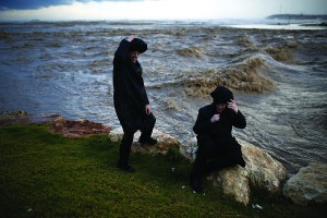 Two men stand next to a stream flowing into the Mediterranean Sea during a rainstorm in the southern city of Ashdod on Wednesday.