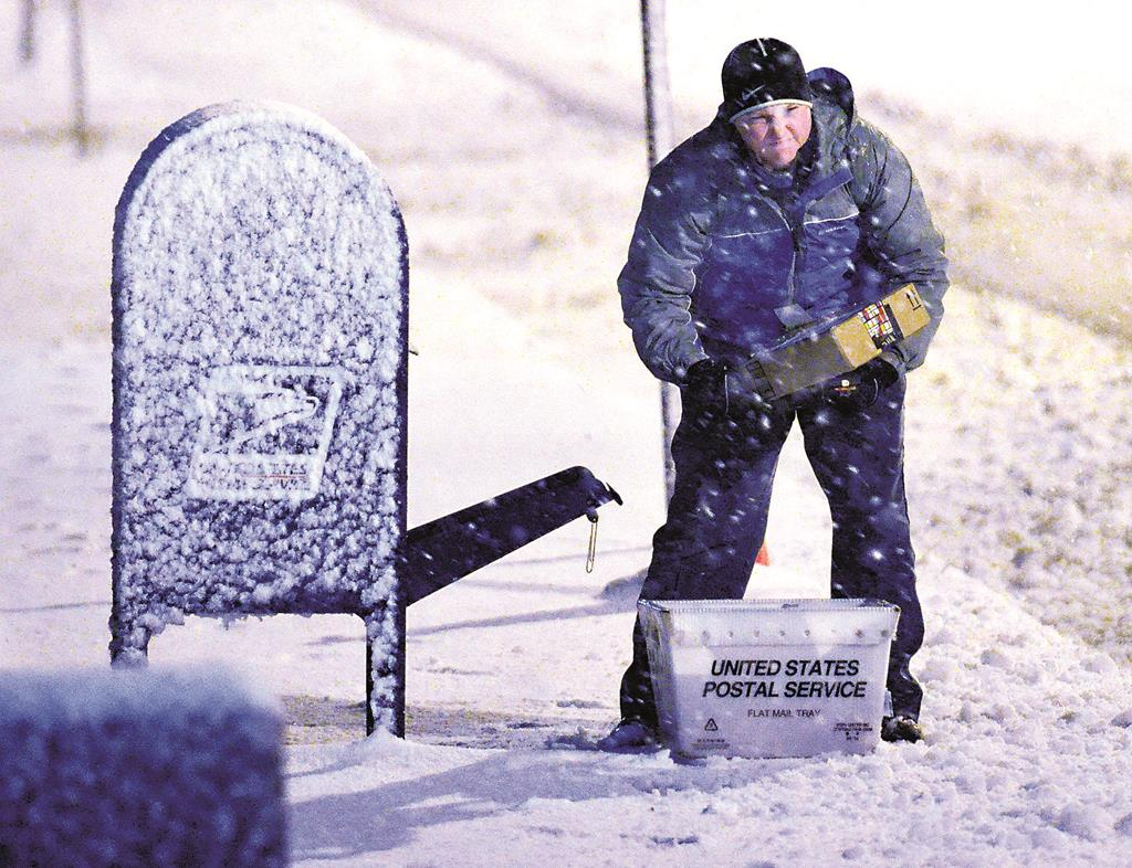 A letter carrier on Tuesday works in heavy snow in Troy, N.Y. (AP Photo/The Saratogian, J.S. Carras)