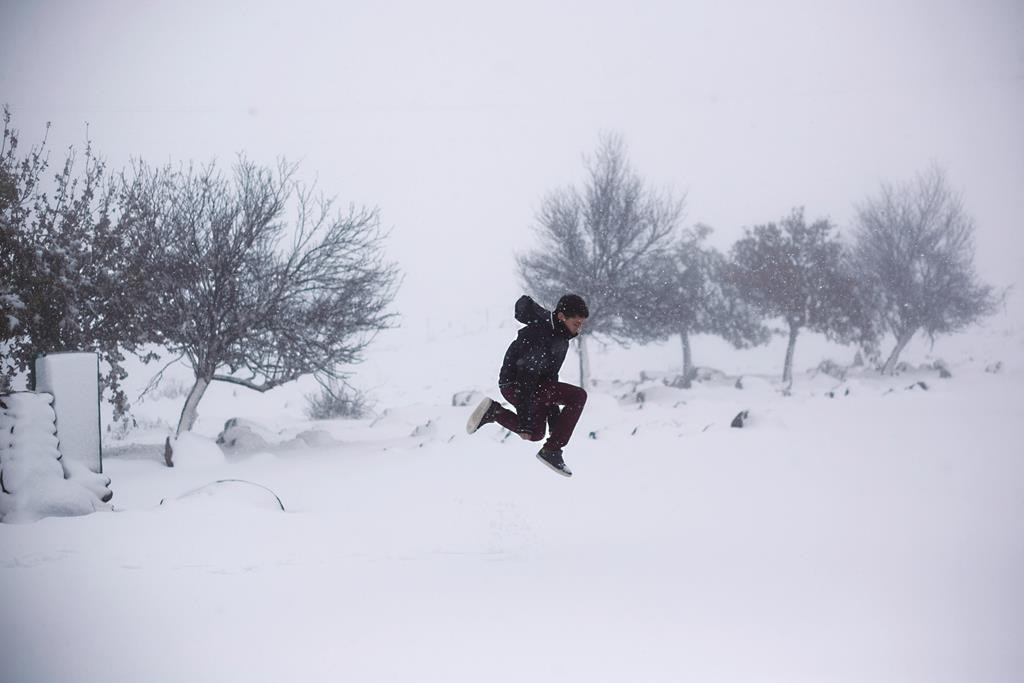 An Israeli boy jumps on the snow in the Israeli-controlled Golan Heights, Wednesday, Jan. 7, 2015. (AP Photo/Ariel Schalit)