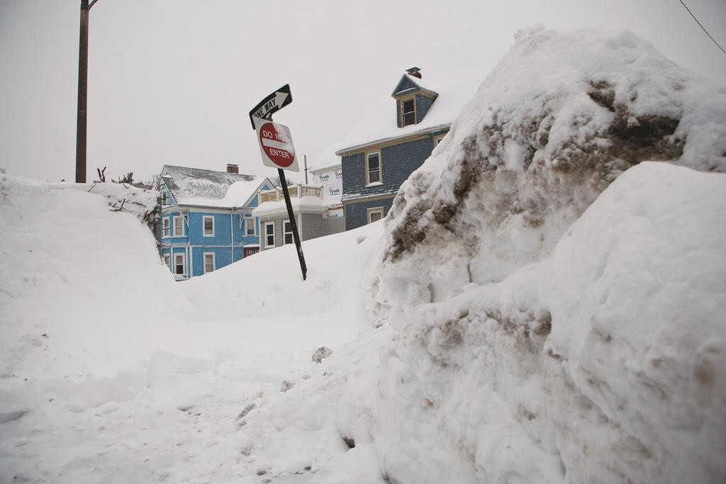 Snowbanks rise as high as street signs on the corner of a residential street in the Dorchester neighborhood of Boston, Massachusetts, Monday.  (Kayana Szymczak/Getty Images)
