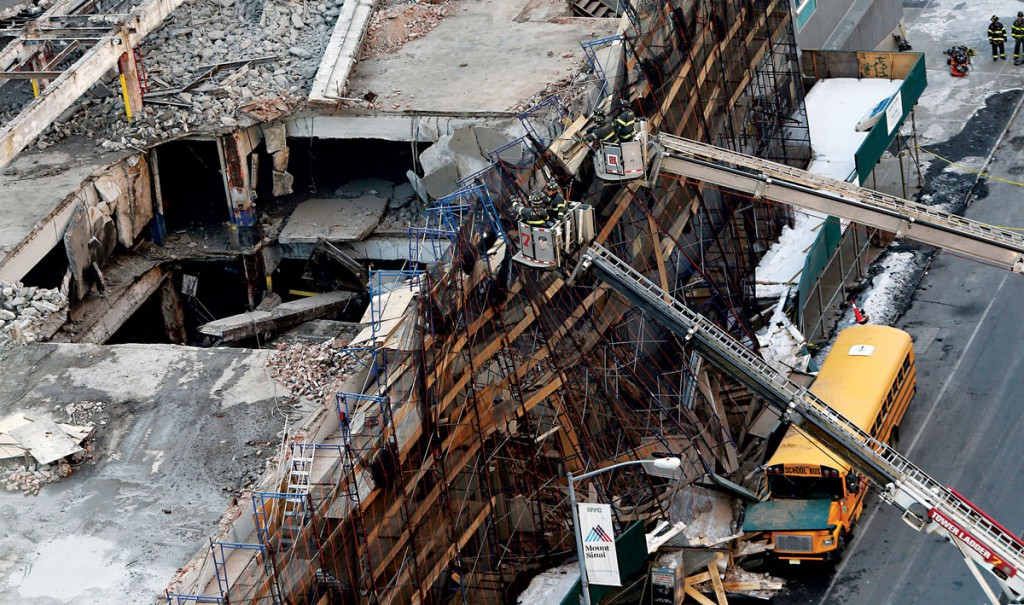 Firefighters survey the outer shell of a midtown Manhattan building that was in the process of being demolished when it partially collapsed on Wednesday. (AP Photo/Kathy Willens)