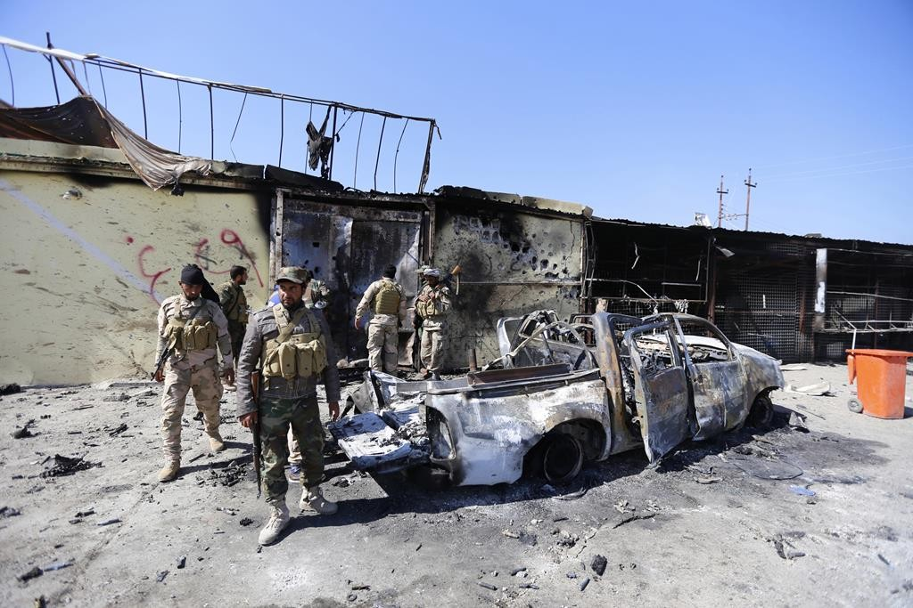 Militias known as Hashid Shaabi inspect a destroyed vehicle of Islamic State in the town of al-Alam Tuesday. (REUTERS/Thaier Al-Sudani)