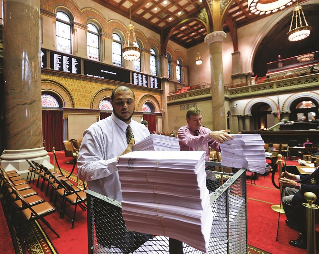 Capitol workers unload budget bills in the Assembly chamber on Tuesday. (AP Photo/Mike Groll)