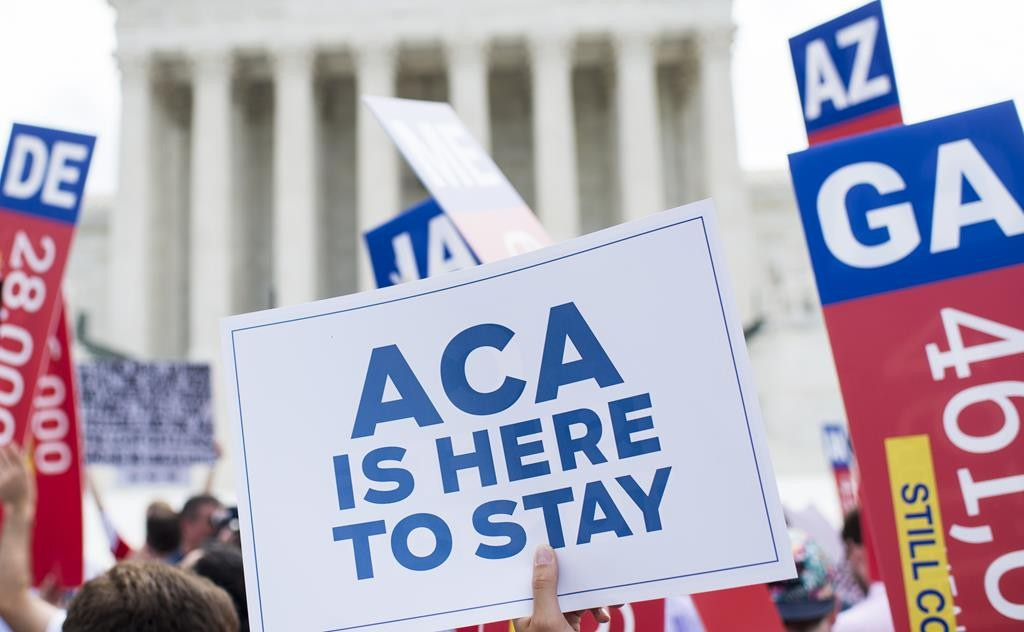 Affordable Care Act supporters wave signs outside the Supreme Court after the court upheld Obamacare on Thursday. (CQ Roll Call via AP Images)