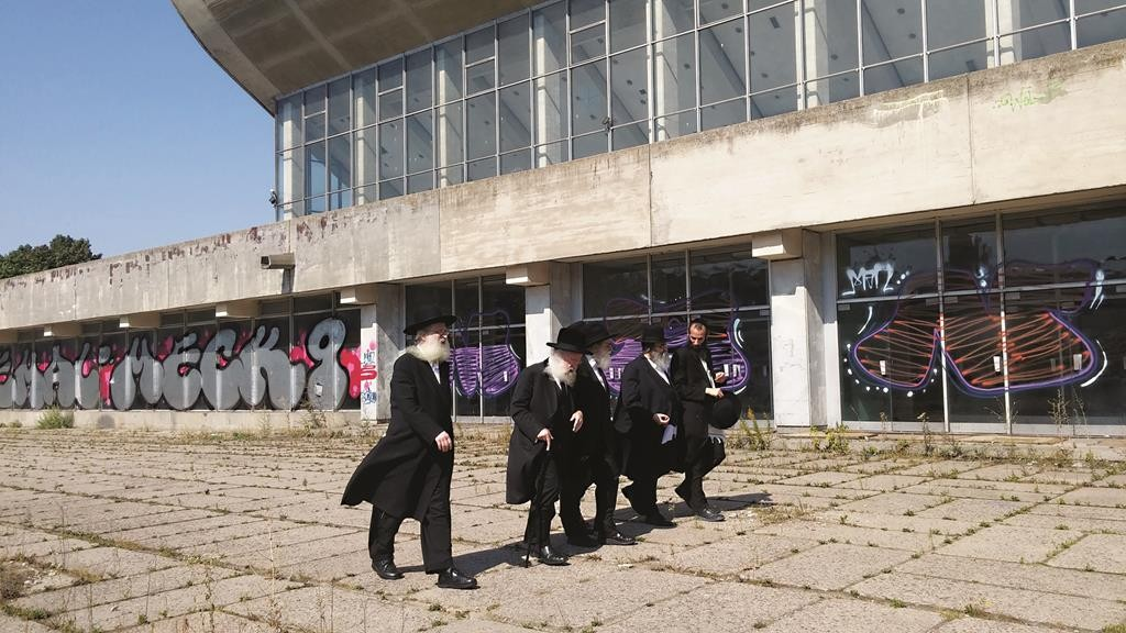 L-R: Harav Osher Kalmanowitz, Harav Schlesinger, Dr. Schaps, Rabbi Niederman, and Rabbi Yechezkel Kalmanowitz outside the abandoned Sports Palace.