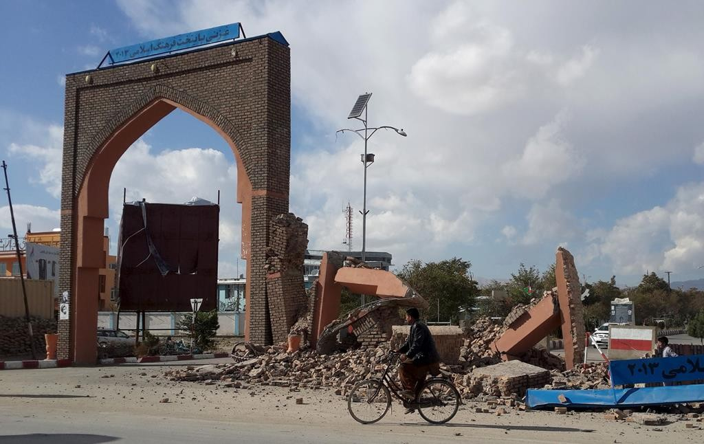 A man rides his bicycle next to damaged structures, after an earthquake in Ghazni, Afghanistan, Monday.  (Reuters/Stringer)