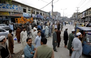 People standing outside their homes and shops during an earthquake in Peshawar, Pakistan, Monday. (AP Photo/Mohammad Sajjad)