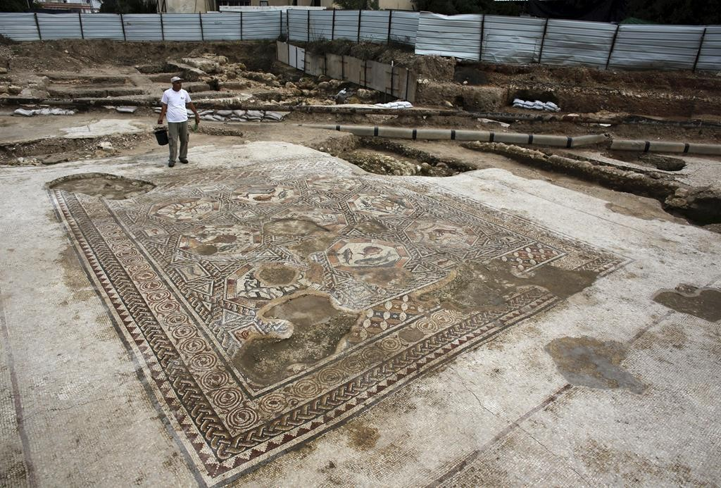 An Israeli antiquity authority worker stands near a mosaic thought to be 1,700 years old, part of a courtyard of a villa, in the present-day city of Lod, south of Tel Aviv, Monday. (REUTERS/Nir Elias)
