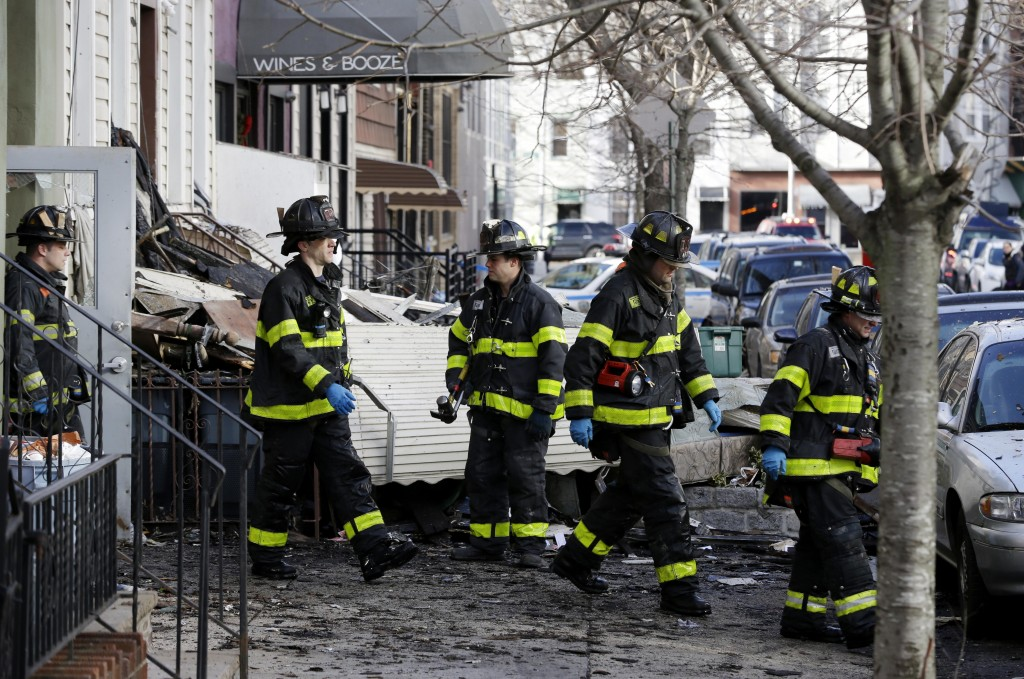 Firefighters leave a building damaged by a fatal fire in Williamsburg on Monday. (AP Photo/Seth Wenig)