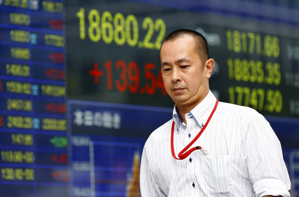 A man walks past an electronic stock indicator of a securities firm in Tokyo, Tuesday, Aug. 25, 2015. Chinese stocks tumbled again Tuesday after their biggest decline in eight years while most other Asian markets rebounded from a day of heavy losses. Tokyo's Nikkei 225 was up 2.1 percent Tuesday after losing 4.6 percent the previous session. (AP Photo/Shizuo Kambayashi)