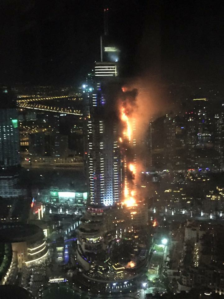 Smoke and flames pour out from a residential building as a fire runs up some 20 stories of a high-rise in Dubai Thursday. (Trevor Hale via AP)