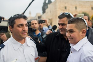 13-year-old Naor Ben-Ezra (Shalev) with paramedic David Dalfan at the Kotel, December 17, 2015, Naor was critically injured in a stabbing attack in Pisgat Zeev in Jerusalem in October. Photo by Yonatan Sindel/Flash90