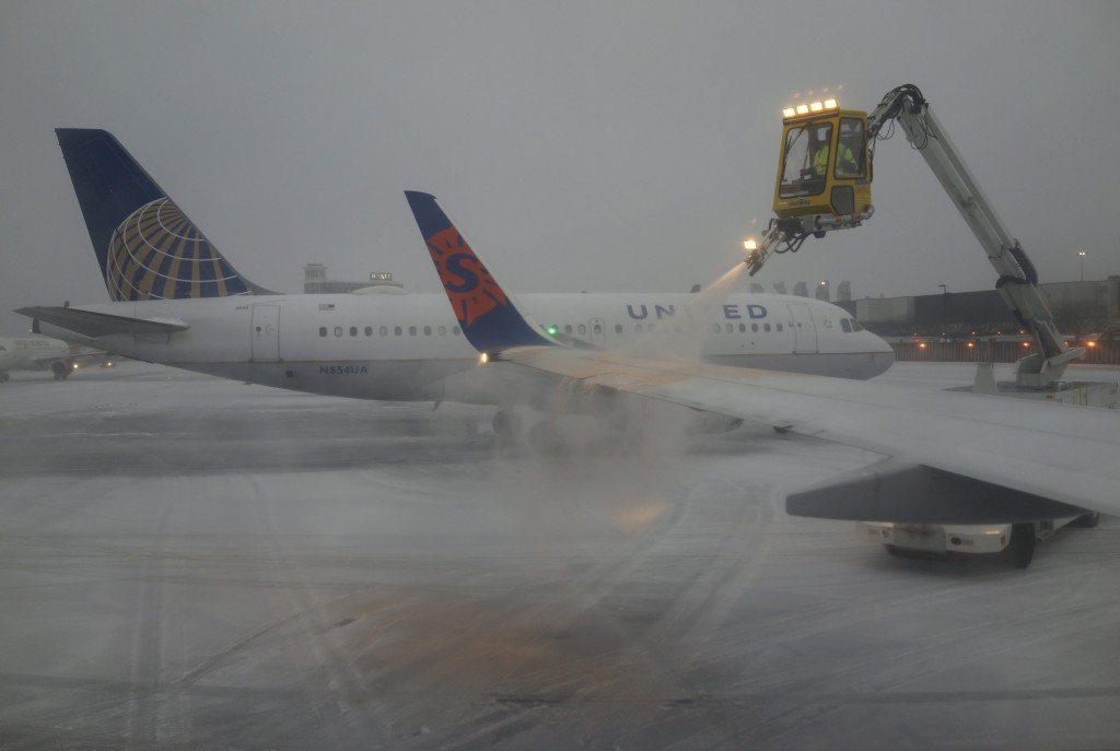 A Sun Country Airlines plane's wing is de-iced as a United Airlines plane waits at the de-icing station during a snowstorm at Logan International Airport in Boston, Massachusetts, United States December 29, 2015. REUTERS/Lucy Nicholson