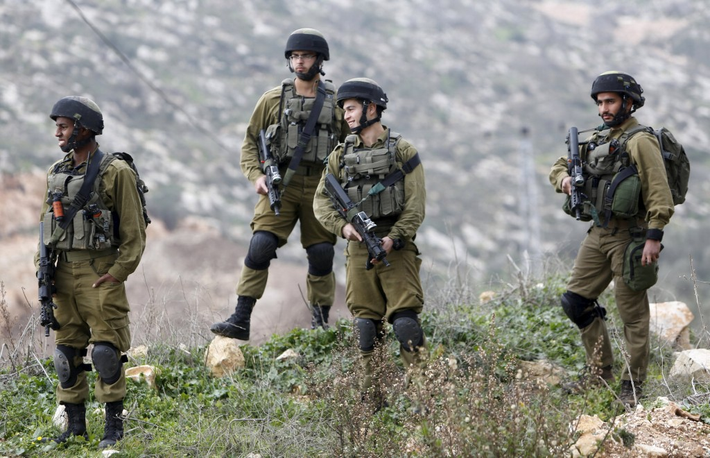 Israeli soldiers stand around near the scene where a Palestinian, who Israeli military said slashed and wounded an army officer, was shot dead by Israeli troops in the West Bank village of Aseera Ashamaliya near Nablus January 14, 2016. Israeli troops killed two knife-wielding Palestinian assailants in the occupied West Bank on Thursday, the army said, the latest in a months-long spate of street violence that Israel's defence minister described as declining. REUTERS/Abed Omar Qusini