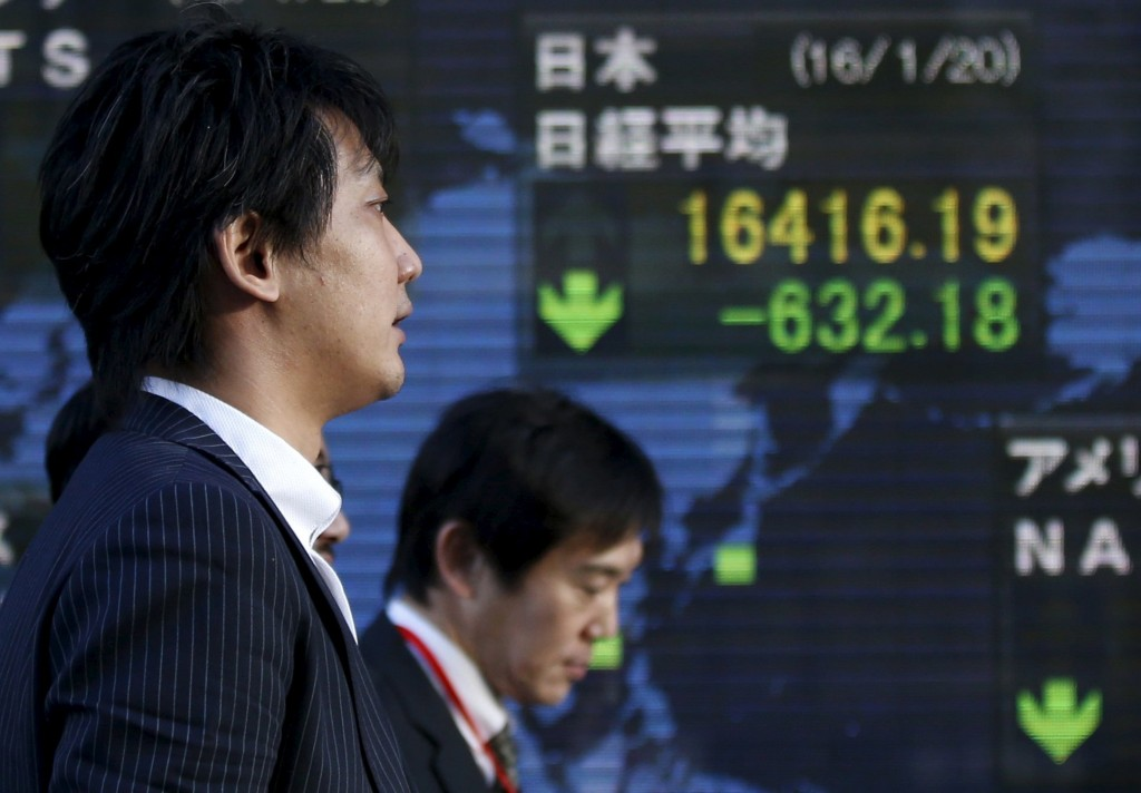 Men walk past an electronic board showing Japan's Nikkei average outside a brokerage in Tokyo, Japan January 20, 2016. Japan's benchmark Nikkei share average tumbled to a fresh 14-1/2 month low on Wednesday as global markets were battered by plunging crude prices that slid to nearly $27 a barrel in the U.S. REUTERS/Toru Hanai