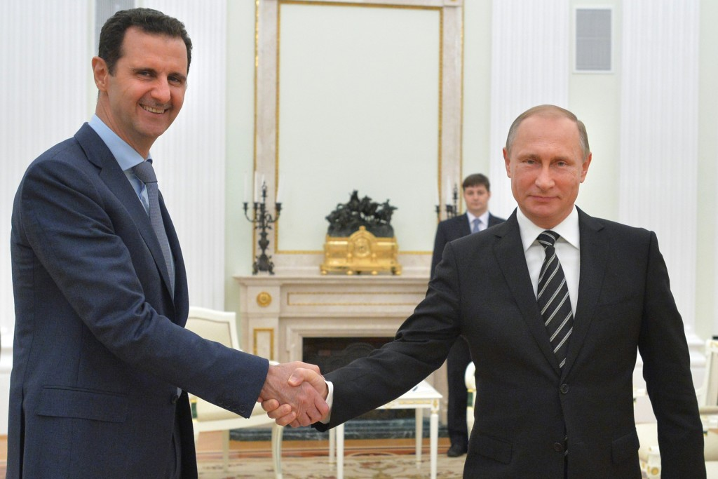 FILE - In this Tuesday, Oct. 20, 2015 file photo, Russian President Vladimir Putin, right, shakes hand with Syria President Bashar Assad in the Kremlin in Moscow, Russia. Russia's involvement in Syria has led to resumed talks about Syria's future in Vienna. So far there's no progress but at least there are talks, notable for including Iran, at Russia's insistence, for the first time. They are notable as well for easing the Kremlin's isolation after its takeover of Crimea and backing for pro-Moscow forces fighting the central government in Ukraine. (Alexei Druzhinin, RIA-Novosti, Kremlin Pool Photo via AP, File)