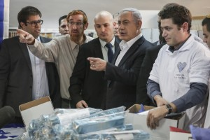 "Prime Minister Benjamin Netanyahu (C), and Likud supporter and activist Yehuda Glick (L) get a tour of the ""Lev HaOlam"" (Heart of the World) organization, in Yerushalayim on February 3, 2015. The organization promotes the export and sale of products from Jewish settlements in Yehudah and Shomron, and aims to fight BDS (boycott) organizations of Israeli settlement products. (Hadas Parush/Flash90/FILE)"