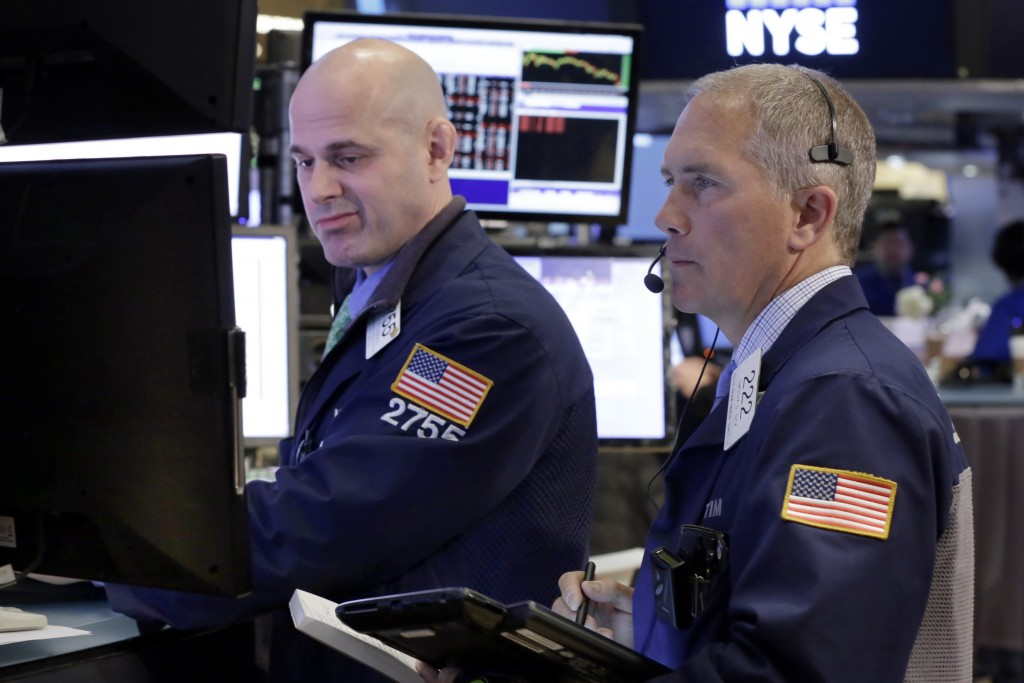 Specialist Mark Fitzgerald, left, and trader Timothy Nick work on the floor of the New York Stock Exchange on Monday. (AP Photo/Richard Drew)