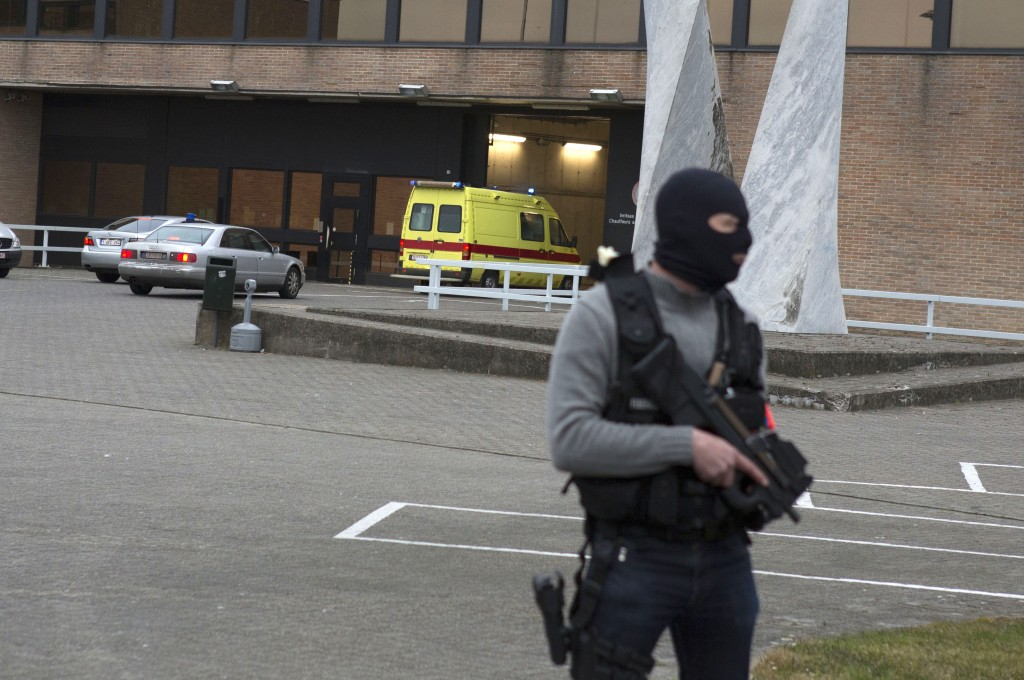"""A special forces police officer guards as a police convoy and ambulance thought to be carrying captured fugitive Salah Abdeslam arrives at the federal penitentiary in Bruges, Belgium, on Saturday, March 19, 2016. Salah Abdeslam, the top suspect in last year's Paris attacks, was charged with """"terrorist murder"""" on Saturday by Belgian authorities and his lawyer vowed to fight any attempt to extradite him to France to stand trial for the slaughter of 130 people. (AP Photo/Geoffroy Van der Hasselt)"""