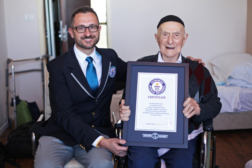 Marco Frigatti, head of records for Guinness World Records, left, presents a certificate to Israel Kristal for being the oldest living man, in Haifa, Israel, on Friday. (Dvir Rosen/Guinness World Records via AP) (Dvir Rosen/Guinness World Records via AP)