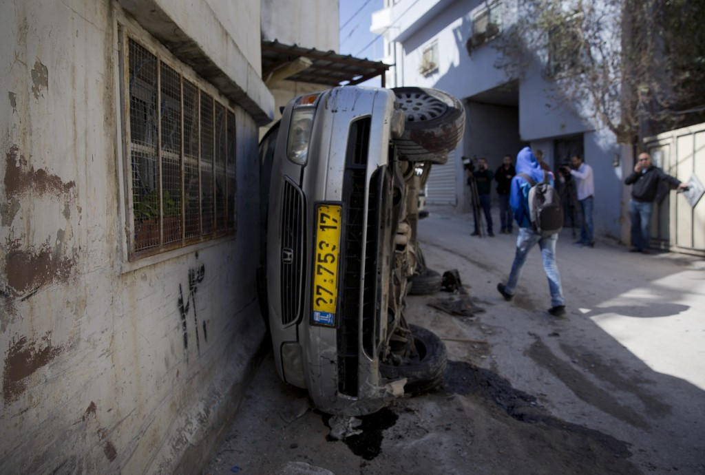A Palestinian man passes a vehicle that was damaged during an Israeli army raid in the West Bank refugee camp of Qalandia, at the outskirts of Ramallah, Tuesday, March 1, 2016. Israeli troops raided a Palestinian refugee camp north of Jerusalem early Tuesday to rescue a pair of soldiers who had lost their way and came under attack in the area, the military said. Palestinian health officials said 22 year-old Palestinian Eyad Sajadiyeh was killed and four others were wounded in the ensuing clashes. (AP Photo/Nasser Nasser)