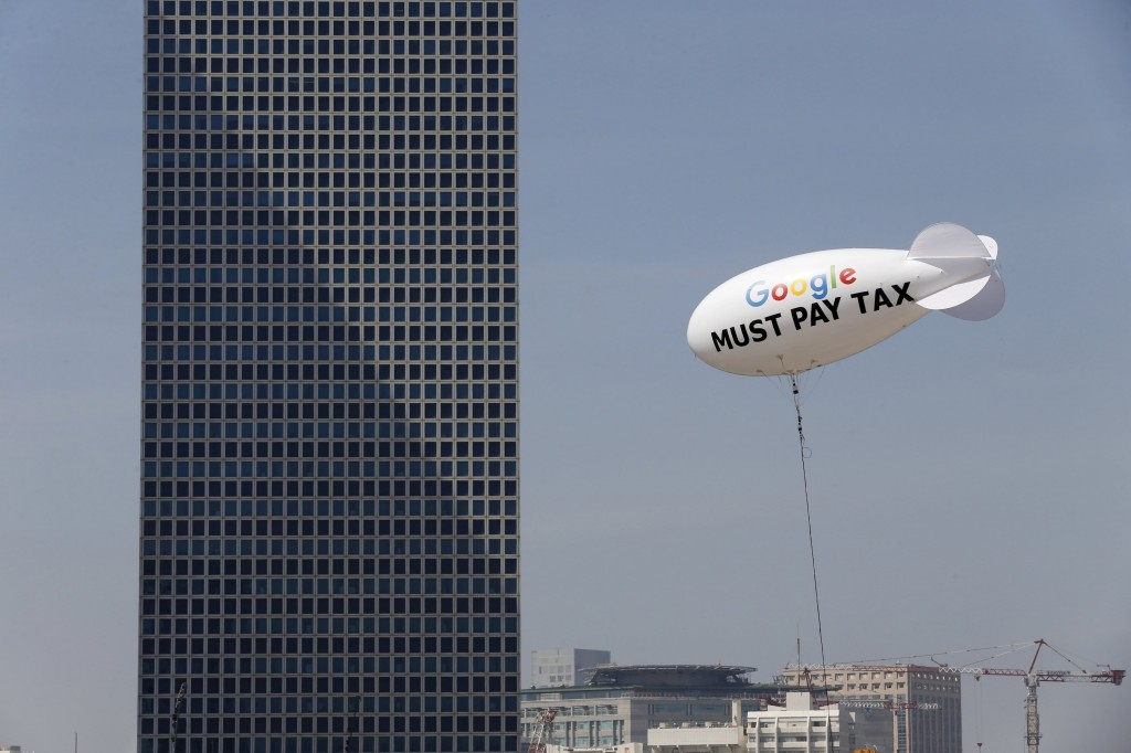 """A blimp reading """"Google must pay tax"""" is seen floating over the Tel Aviv skyline inthis April 3, 2016 file photo. REUTERS/Baz Ratner/Files"""