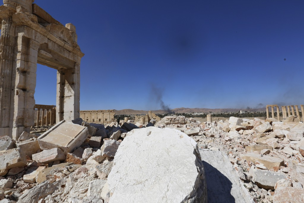 In this picture taken Friday, smoke rises in the distance as damage is seen at an historical site in Palmyra in the central city of Homs, Syria. (AP Photo)