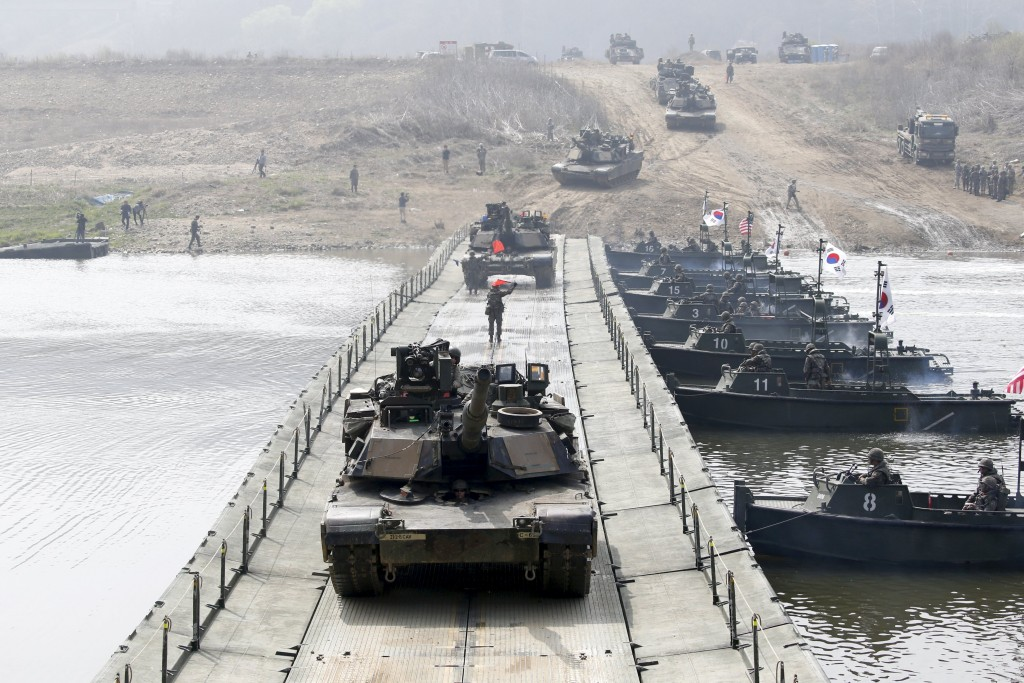 U.S. army M1A2 tanks cross a pontoon bridge during a U.S.-South Korea joint river-crossing exercise near the demilitarized zone separating the two Koreas in Yeoncheon, South Korea, April 8, 2016. REUTERS/Kim Hong-Ji