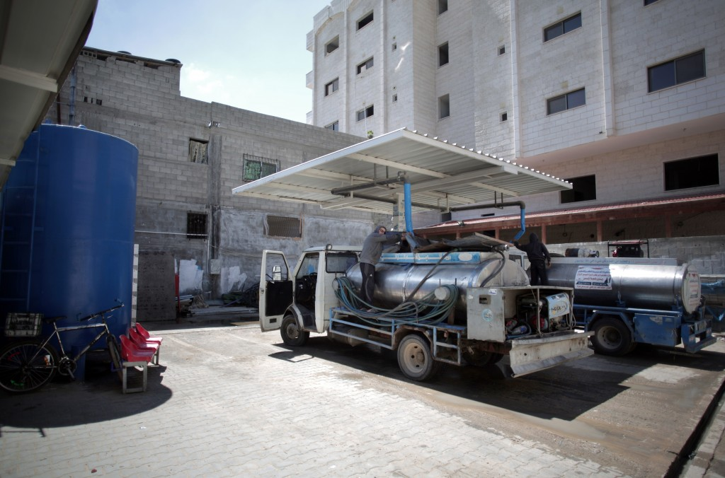 In this Thursday, April 14, 2016 photo, A Palestinian man fills tankers with water to sell at a drinking water station in Gaza City. Poor sewage treatment is a feature of life in Gaza, a result of the rapidly expanding population, an infrastructure damaged during wars with Israel and a chronic shortage of electricity to run the wastewater plants that still function. (AP Photo/Khalil Hamra)