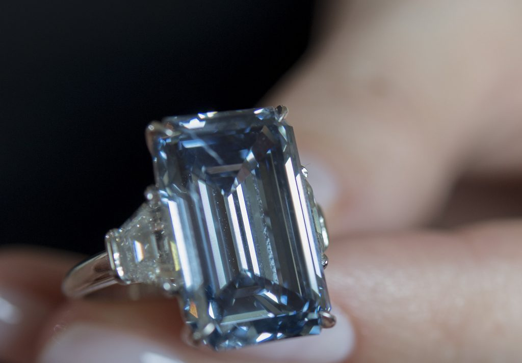 A Christie's employee holds Oppenheimer Blue diamond of 14.62 carats, which is estimated to be sold between 38,000,000 to 45,000,000 US Dollars, during a preview at the auction house Christie's, in Geneva, Switzerland, Thursday, May 12, 2016. The auction will take place on May 18, 2016 in Geneva. (Martial Trezzini/Keystone via AP)