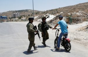 Israeli soldiers stop a Palestinian on his bicycle at the entrance of Yatta near the West Bank city of Hebron June 9, 2016. REUTERS/Mussa Qawasma       TPX IMAGES OF THE DAY