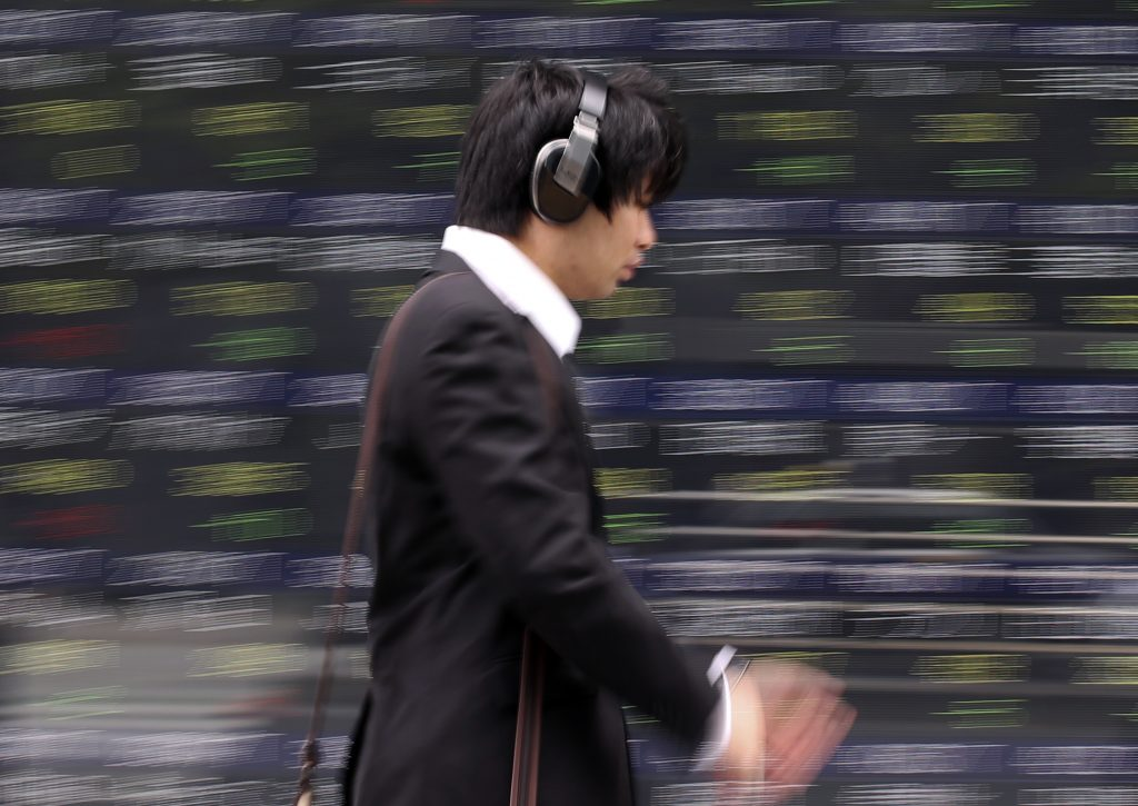 A man walks by an electronic stock board of a securities firm in Tokyo, Monday, June 6, 2016. Asian shares were mostly lower Monday as a U.S. report that showed slowing hiring was seen as making a Federal Reserve rate hike as less likely but sent the dollar lower and fanned fears about the American economy. (AP Photo/Koji Sasahara)