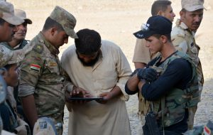 A displaced man from south of Mosul gives the coordinates of Islamic State terrorists to Iraqi army personnel south of Mosul on Friday. (Reuters/Stringer)